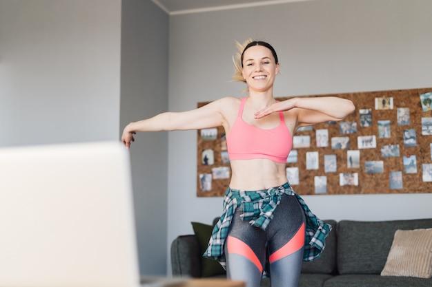 Mulher sorridente dançando no meio da sala de estar se divertindo e vida