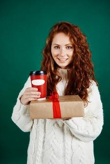 Mulher sorridente dando um presente e um café