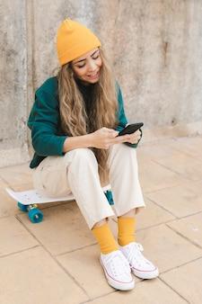Mulher sorridente de alto ângulo sentado no skate