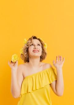 Mulher sorridente de baixo ângulo com flores amarelas