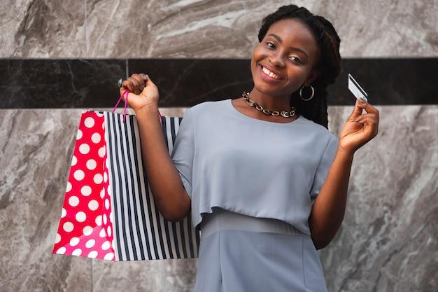 Mulher sorridente de baixo ângulo com sacos de compras