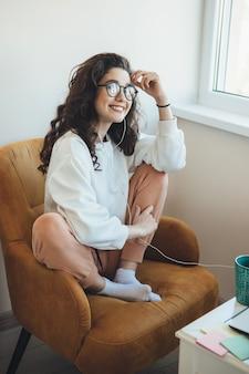 Mulher sorridente de cabelos cacheados está ouvindo aulas online no laptop enquanto bebe uma xícara de chá