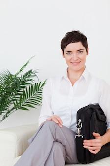 Mulher sorridente de cabelos curtos sentado em um sofá