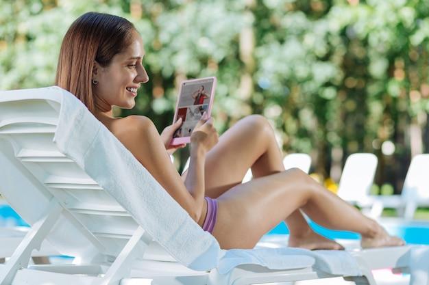 Mulher sorridente de cabelos escuros assistindo a um vídeo engraçado no laptop deitado sob o sol