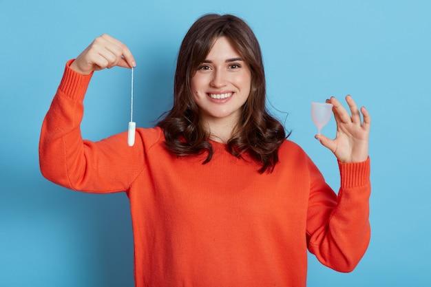 Mulher sorridente de cabelos escuros compara duas variantes de higiene feminina, segurando um tampão de algodão e um copo menstrual isolado sobre uma parede azul