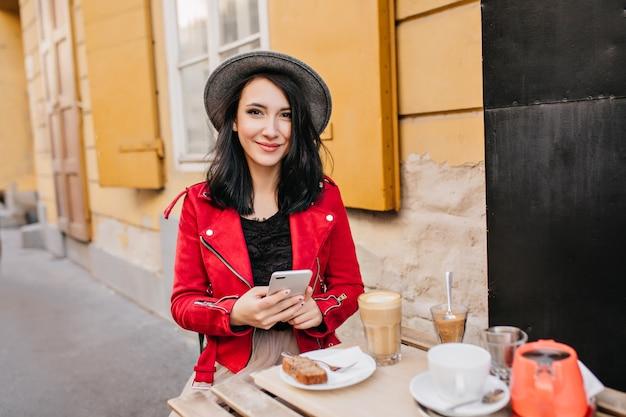 Mulher sorridente de cabelos negros com telefone sentada em um café ao ar livre pela manhã
