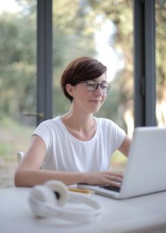 Mulher sorridente de cabelos negros trabalhando em seu laptop na sala