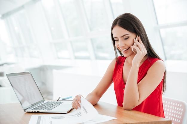 Mulher sorridente de camisa vermelha falando no telefone e sentada à mesa com o laptop no escritório