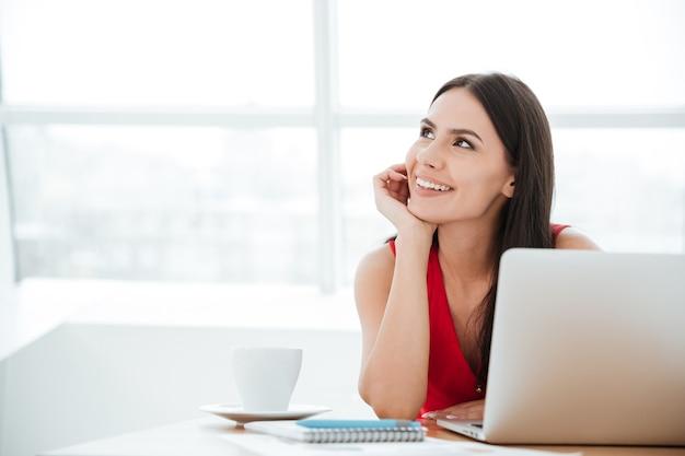 Mulher sorridente de camisa vermelha sentada à mesa com o laptop no escritório e olhando para longe