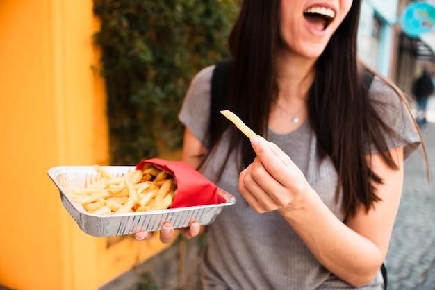 Mulher sorridente de close-up com batatas fritas