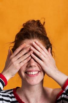 Mulher sorridente de close-up com fundo laranja, cobrindo os olhos