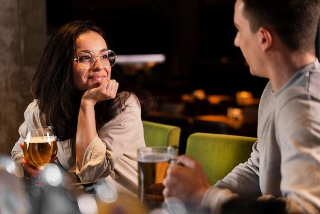 Mulher sorridente de close-up e homem com cerveja