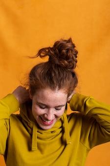 Mulher sorridente de close-up, organizando seu capuz amarelo