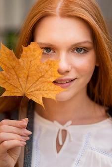 Mulher sorridente de close-up, segurando a folha