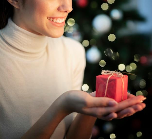 Mulher sorridente de close-up, segurando o pequeno presente