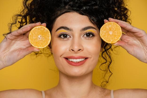 Mulher sorridente de close-up segurando rodelas de limão