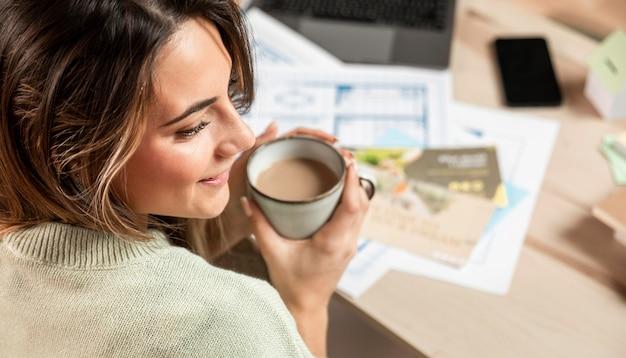 Mulher sorridente de close-up segurando uma xícara de café