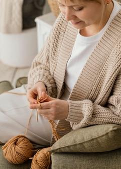 Mulher sorridente de close-up tricotando