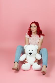 Mulher sorridente de corpo inteiro em jeans com cabelo vermelho segurando um grande ursinho de pelúcia branco entre as pernas