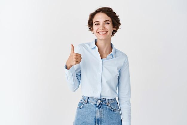 Mulher sorridente de escritório profissional aparece com o polegar, parecendo satisfeita, aprova e recomenda a empresa, elogia o bom trabalho, diga bem feito, em pé na parede branca