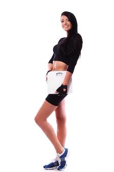 Mulher sorridente de fitness segurando balanças