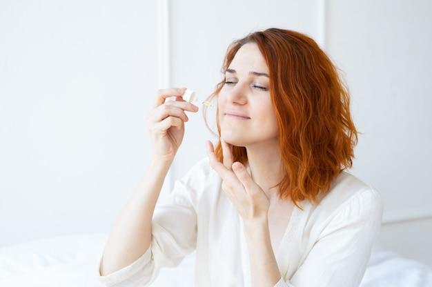 Mulher sorridente de gengibre em roupão de seda com óleo cosmético para o rosto em sala de luz, mime-se.