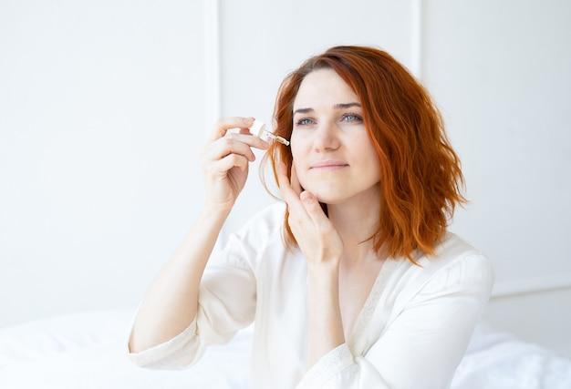 Mulher sorridente de gengibre em um robe de seda com óleo cosmético para o rosto em uma sala iluminada.
