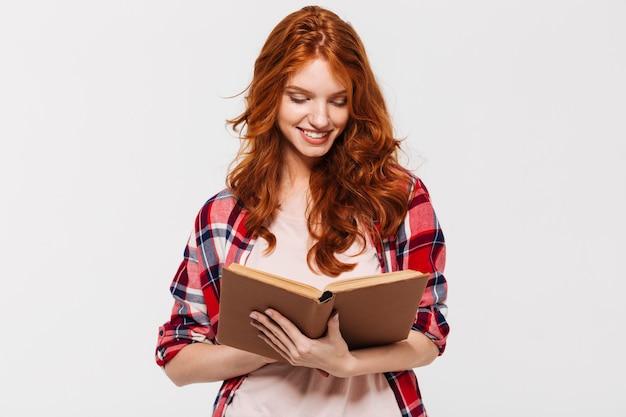 Mulher sorridente de gengibre na camisa segurando e lendo o livro