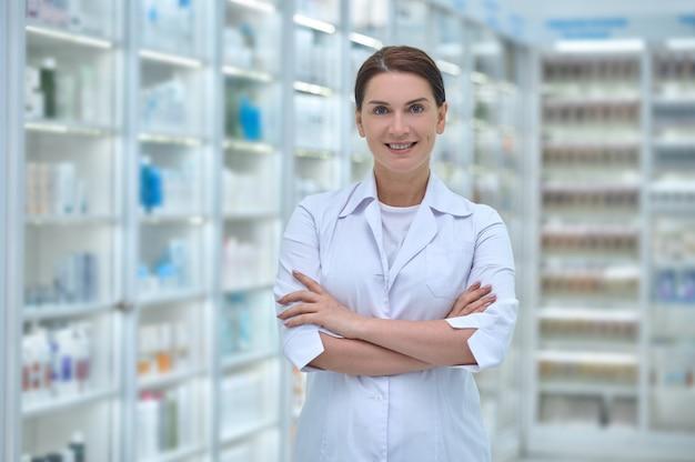 Mulher sorridente de jaleco branco na farmácia