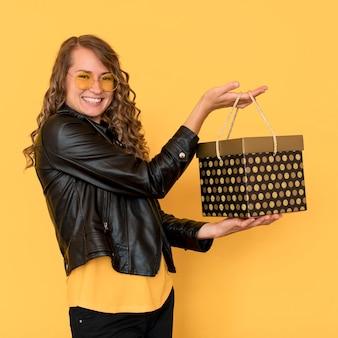 Mulher sorridente de lado segurando uma caixa preta de presente sexta-feira