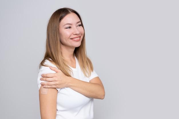Mulher sorridente de meia-idade com um curativo ou adesivo na mão recebendo uma vacina