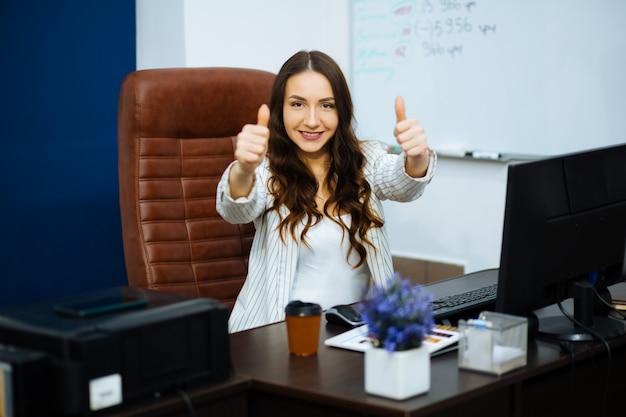 Mulher sorridente de negócios com cabelos ondulados escuros, sentado na mesa perto do computador, mostrando o gesto com dois dedos para a frente