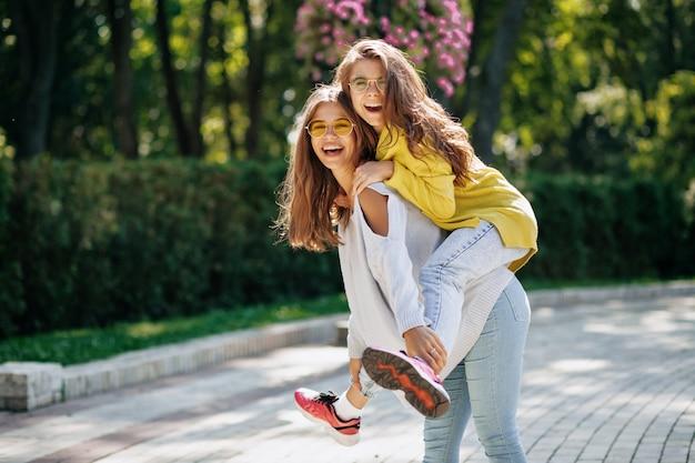 Mulher sorridente de óculos brilhantes e pulôver, posando com um amigo animado ao ar livre, se divertindo e brincando. retrato de lindas jovens elegantes com cabelos castanhos