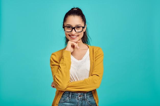 Mulher sorridente de óculos, parede azul, emoção positiva. expressão facial, pessoa do sexo feminino olhando para a câmera no estúdio, conceito emocional, sentimentos