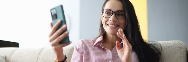 Mulher sorridente de óculos se senta no sofá, segura o smartphone e acena para a tela.