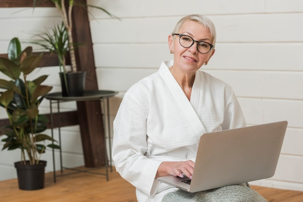 Mulher sorridente de óculos, segurando um laptop