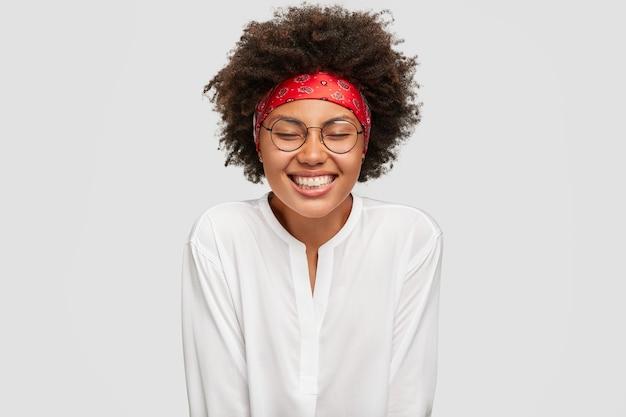 Mulher sorridente de pele escura com expressão de satisfação satisfeita, se sente feliz por estar de bom humor