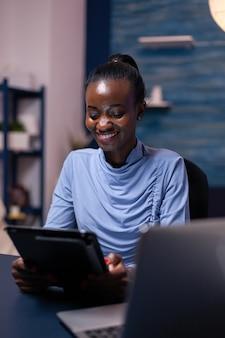 Mulher sorridente de pele escura navegando no tablet pc do escritório em casa tarde da noite. funcionário com foco ocupado usando rede de tecnologia moderna sem fio fazendo horas extras.