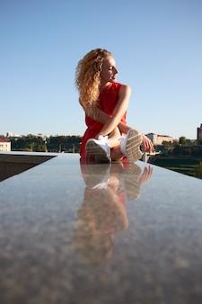 Mulher sorridente de penteado encaracolado redgead jovem, weared no vestido vermelho, retrato urbano ao ar livre