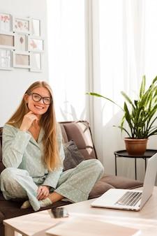Mulher sorridente de pijama, trabalhando em casa