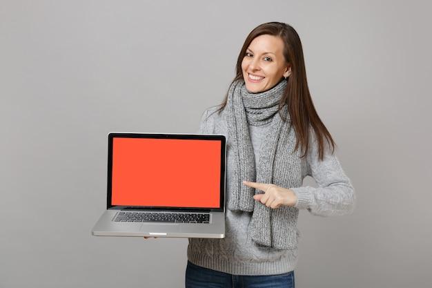Mulher sorridente de suéter cinza, dedo indicador de ponto de lenço no computador laptop pc com tela vazia em branco isolada no fundo cinza. estilo de vida saudável, consultoria de tratamento online, conceito de estação fria.