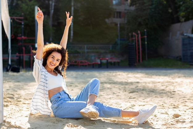Mulher sorridente de tiro certeiro posando ao lado de um campo de vôlei