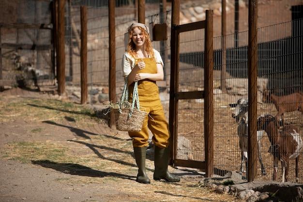Mulher sorridente de tiro completo e cabras