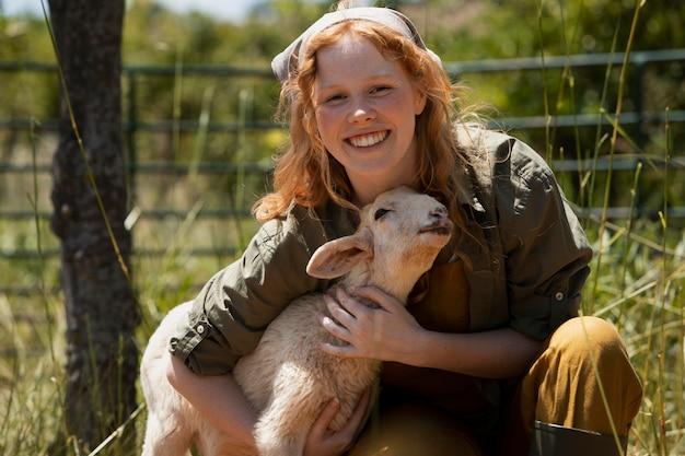 Mulher sorridente de tiro médio abraçando um cordeiro