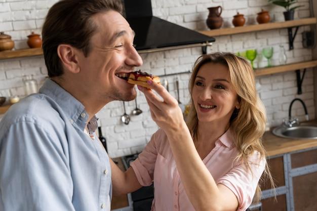 Mulher sorridente de tiro médio alimentando homem