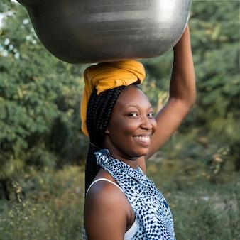 Mulher sorridente de tiro médio carregando tigela