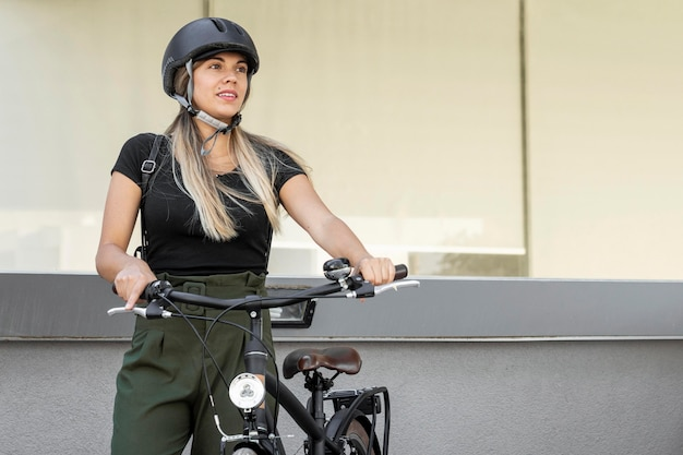Mulher sorridente de tiro médio com bicicleta