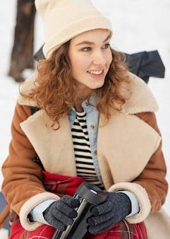 Mulher sorridente de tiro médio com garrafa térmica