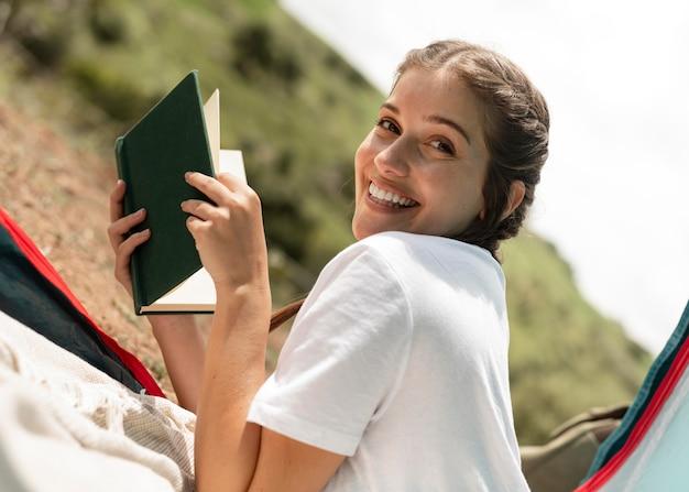 Mulher sorridente de tiro médio com livro