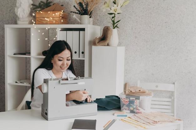 Mulher sorridente de tiro médio com máquina de costura
